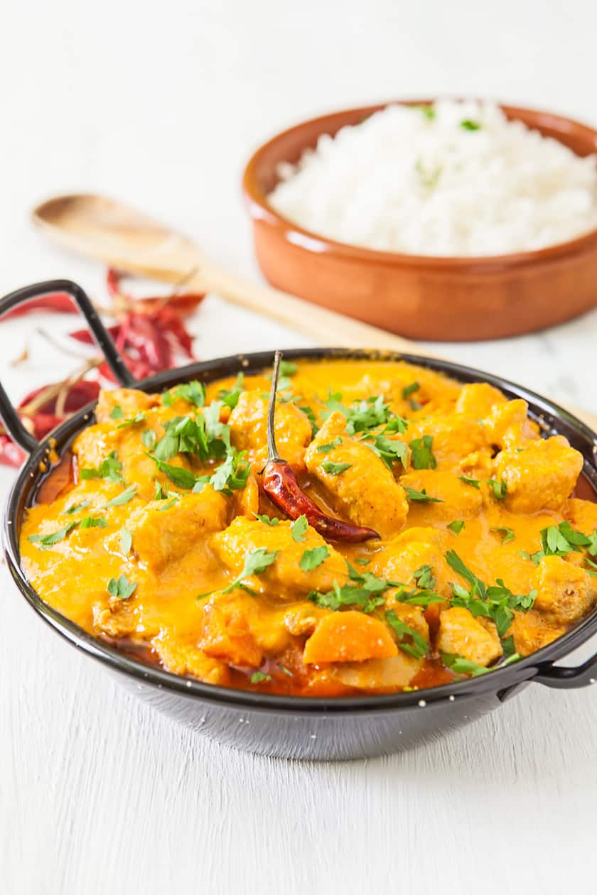 Pot of Chicken Curry with White Rice in the Background