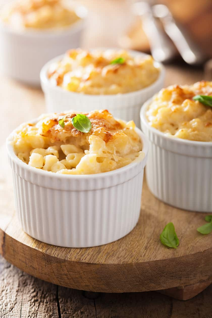 Closeup of individual baked mac and cheese on a wood board