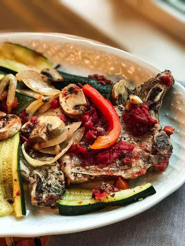 Italian Pork Chops and Vegetables on a White Platter