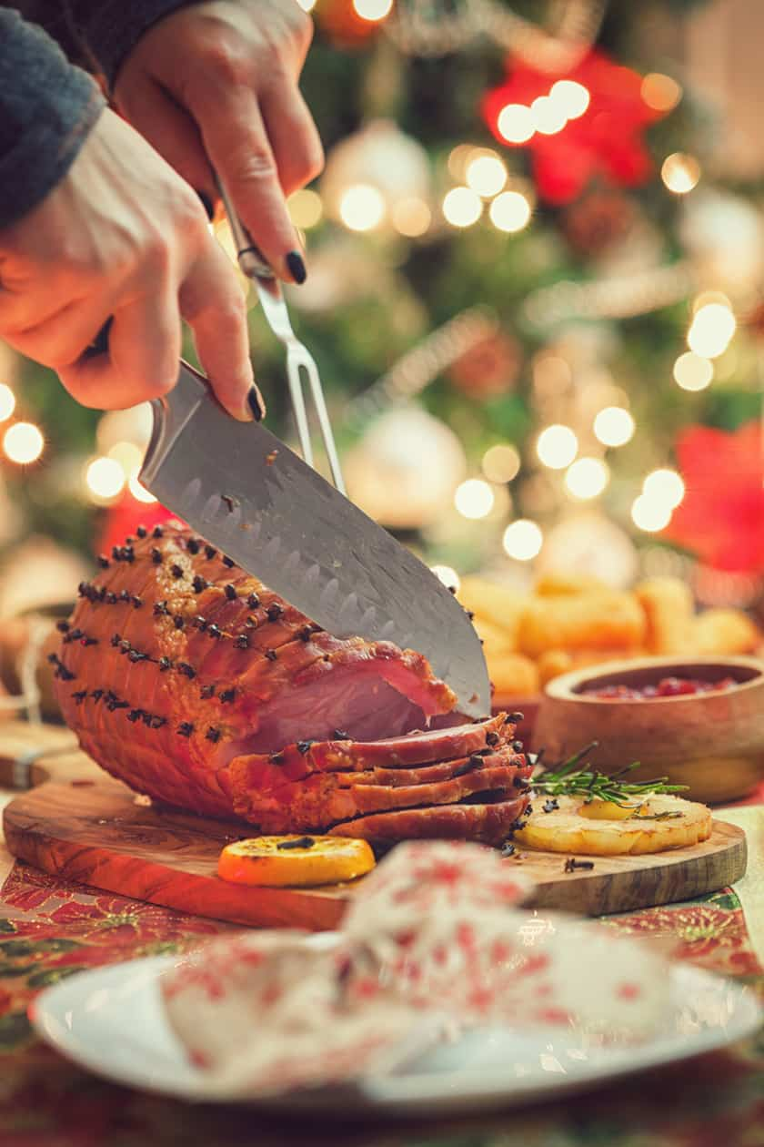 Slicing Ham in front of a Christmas Tree