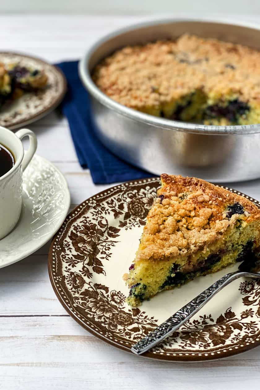 Slice of Blueberry Buckle Coffee Cake with a Cup of Coffee