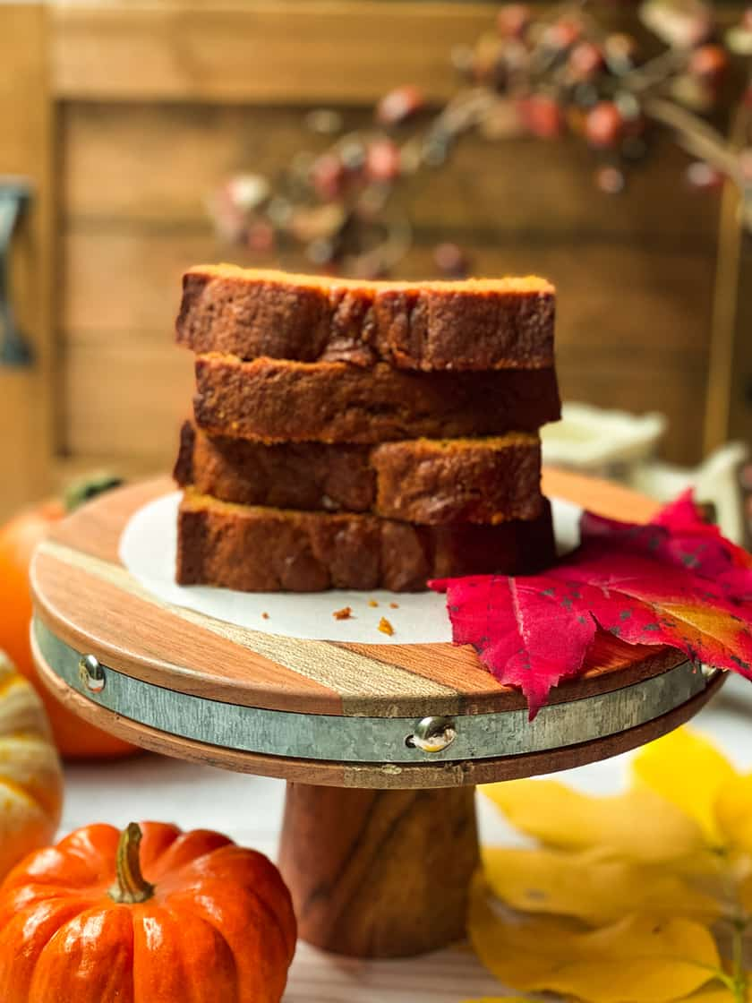 Sliced and Stacked Pumpkin Bread on a Wood Serving Platter