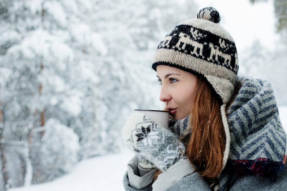 Woman sipping cocoa in the snow