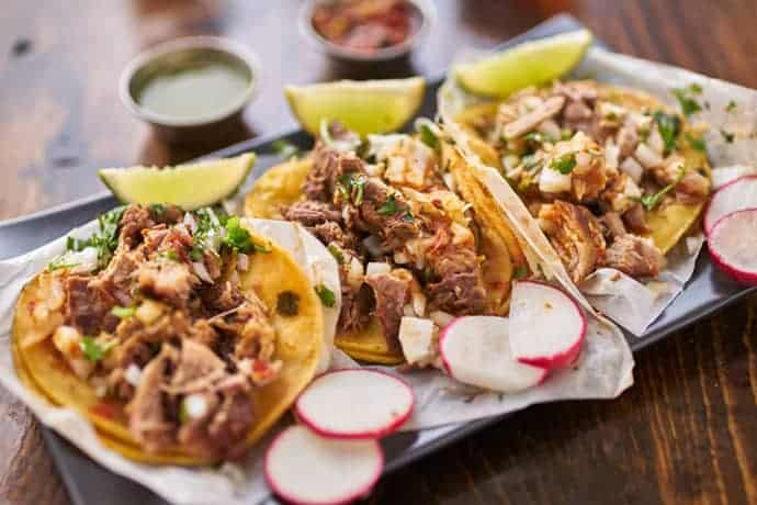 Chicken Tacos with lime, shredded chicken, and radishes