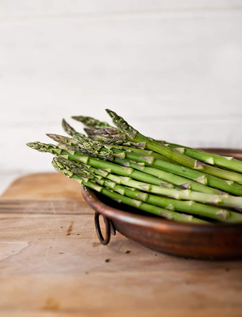 fresh asparagus spears in a copper pot