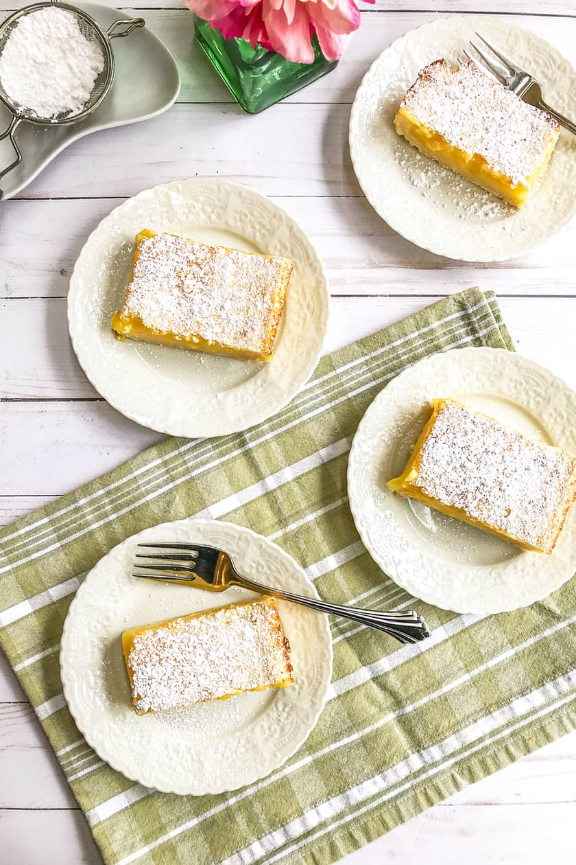 Top view of squares of lemon bars on a green backdrop
