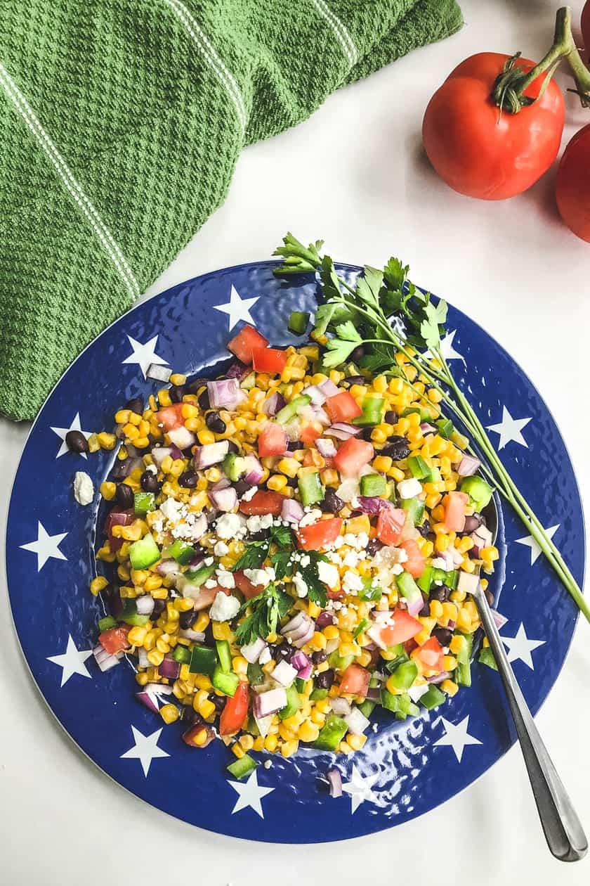 Mexican Corn Salad on plate with fresh tomatoes