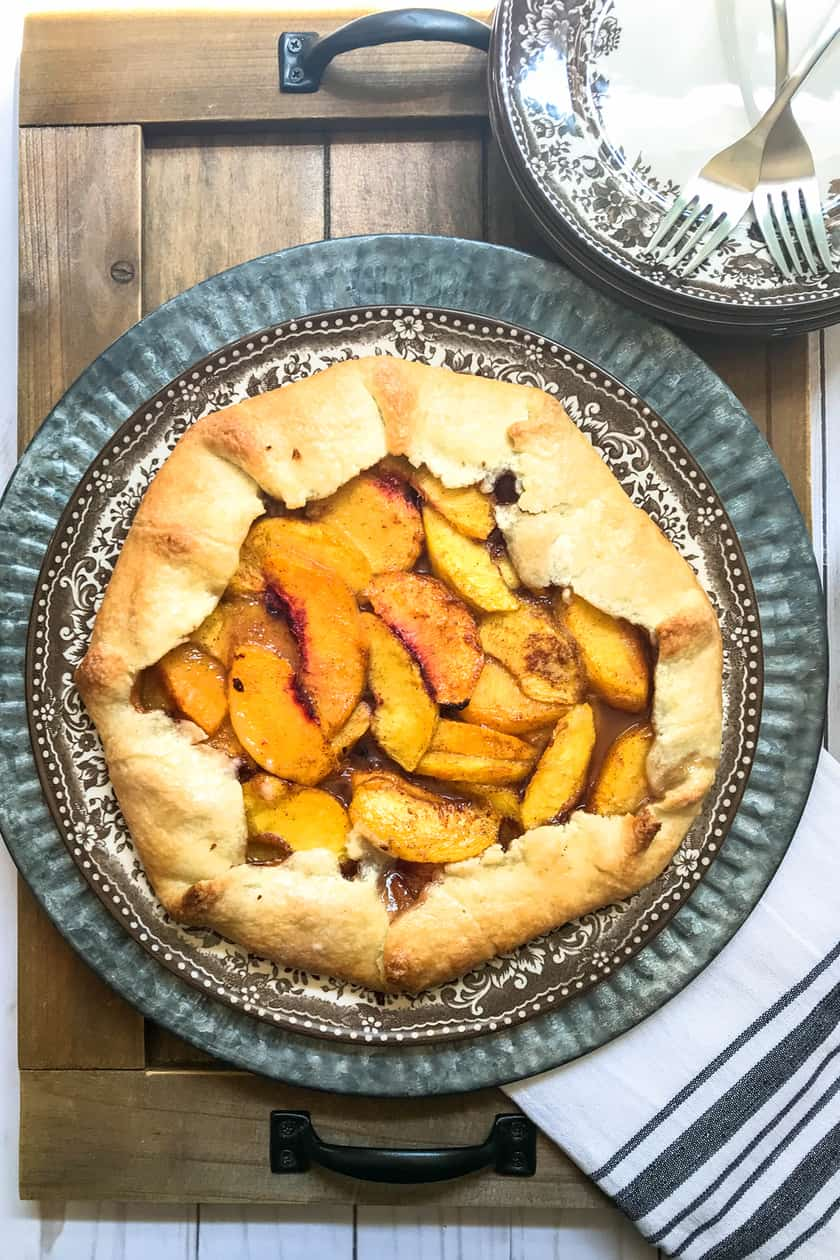 Overhead photo of peach galette on a silver plate