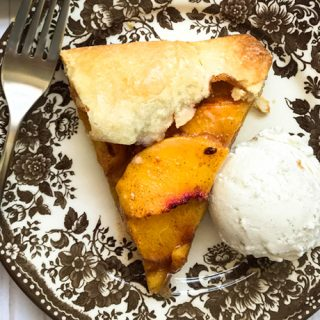 closeup of peach galette with ice cream
