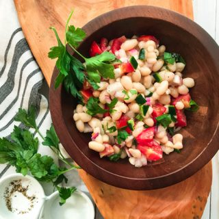 closeup of white bean salad in a wooden bowl