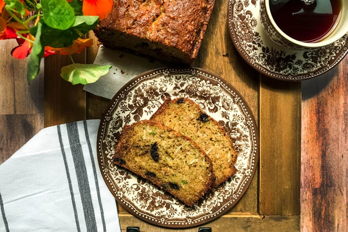 slice of chocolate chunk zucchini bread with a cup of coffee