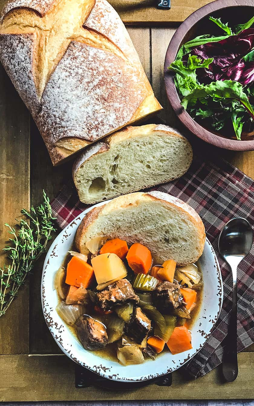 Scottish Beef Stew with Sliced Bread on Wooden Board
