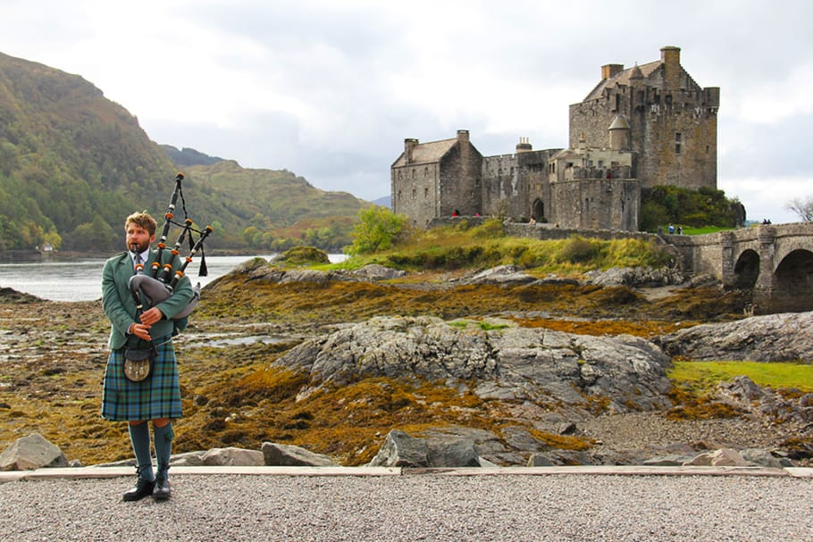 bagpipes in front of Scottish castle ruins
