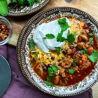 Bowl of Instant Pot Turkey Chili with Sour Cream and Cilantro
