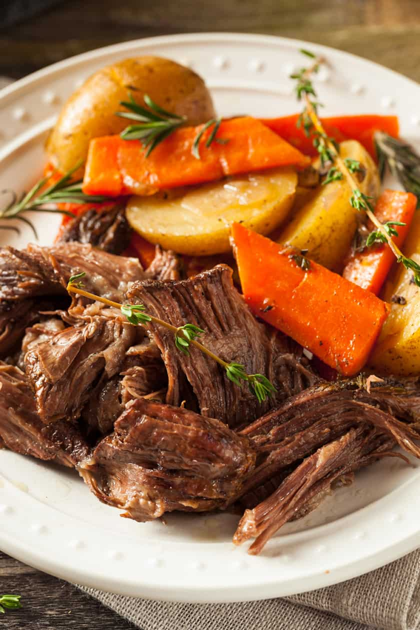 closeup of a bowl of beef post roast with carrots and potatoes