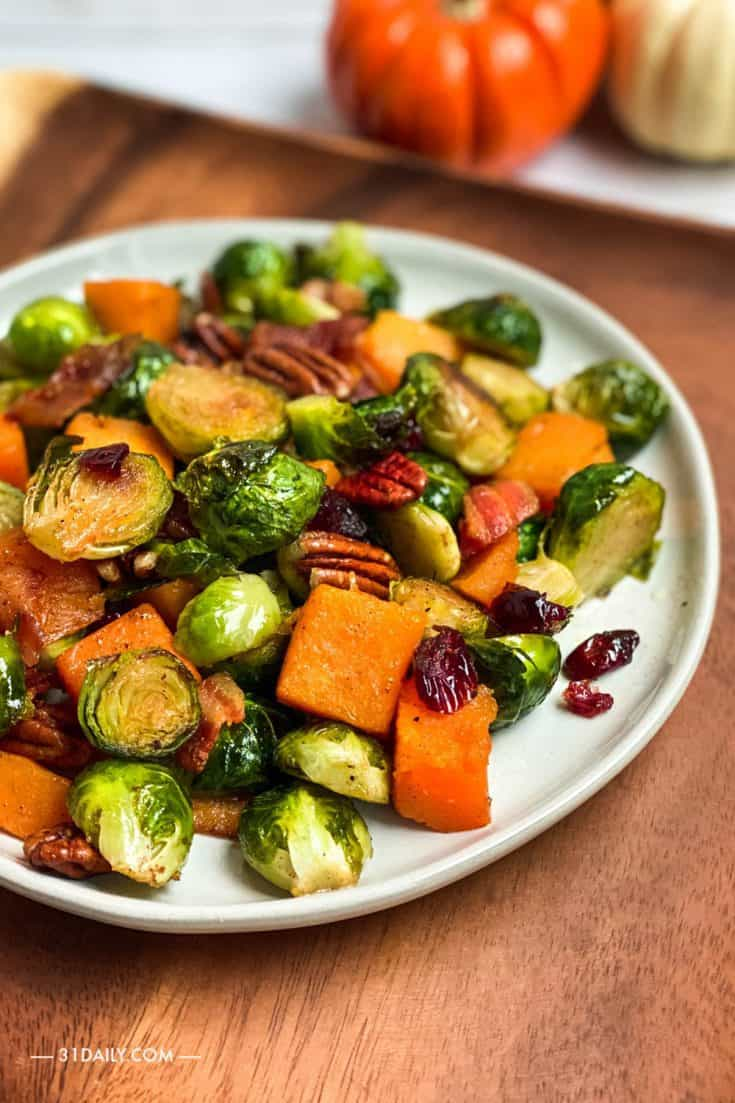 Maple Glazed Roasted Brussels Sprouts and Butternut Squash with dried cranberries, toasted pecans, and crispy bacon. Literally, the perfect Thanksgiving side. Maple Glazed Roasted Brussels Sprouts and Butternut Squash | 31Daily.com #vegetables #brusselssprouts #butternut #roastedvegetables #sheetpan #thanksgiving #christmas #sides #31Daily