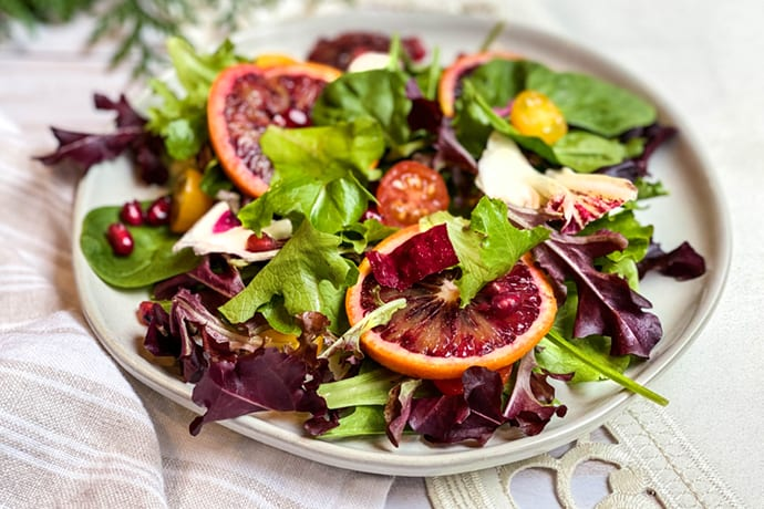 Closeup of winter greens salad with slices of blood oranges