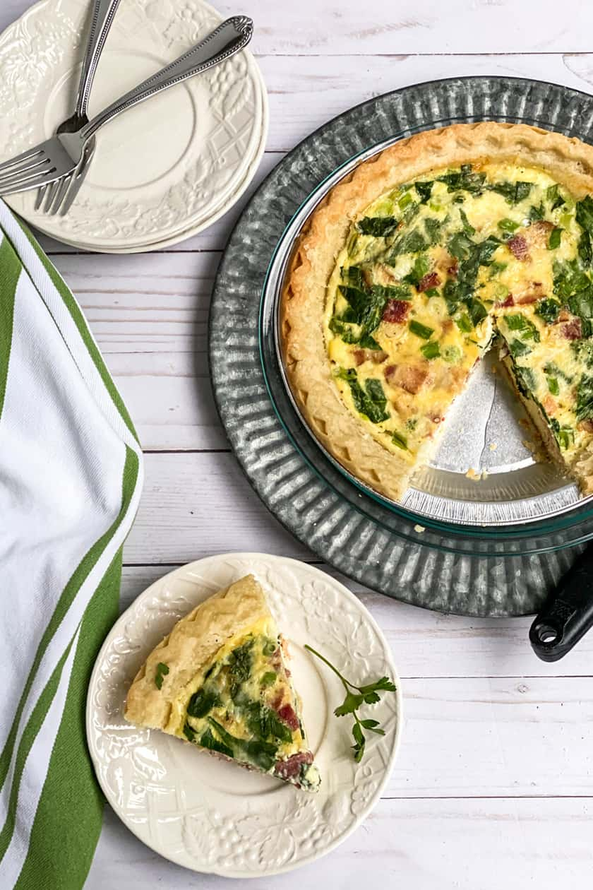 Baked Make Ahead Quiche with a Slice on a White Plate