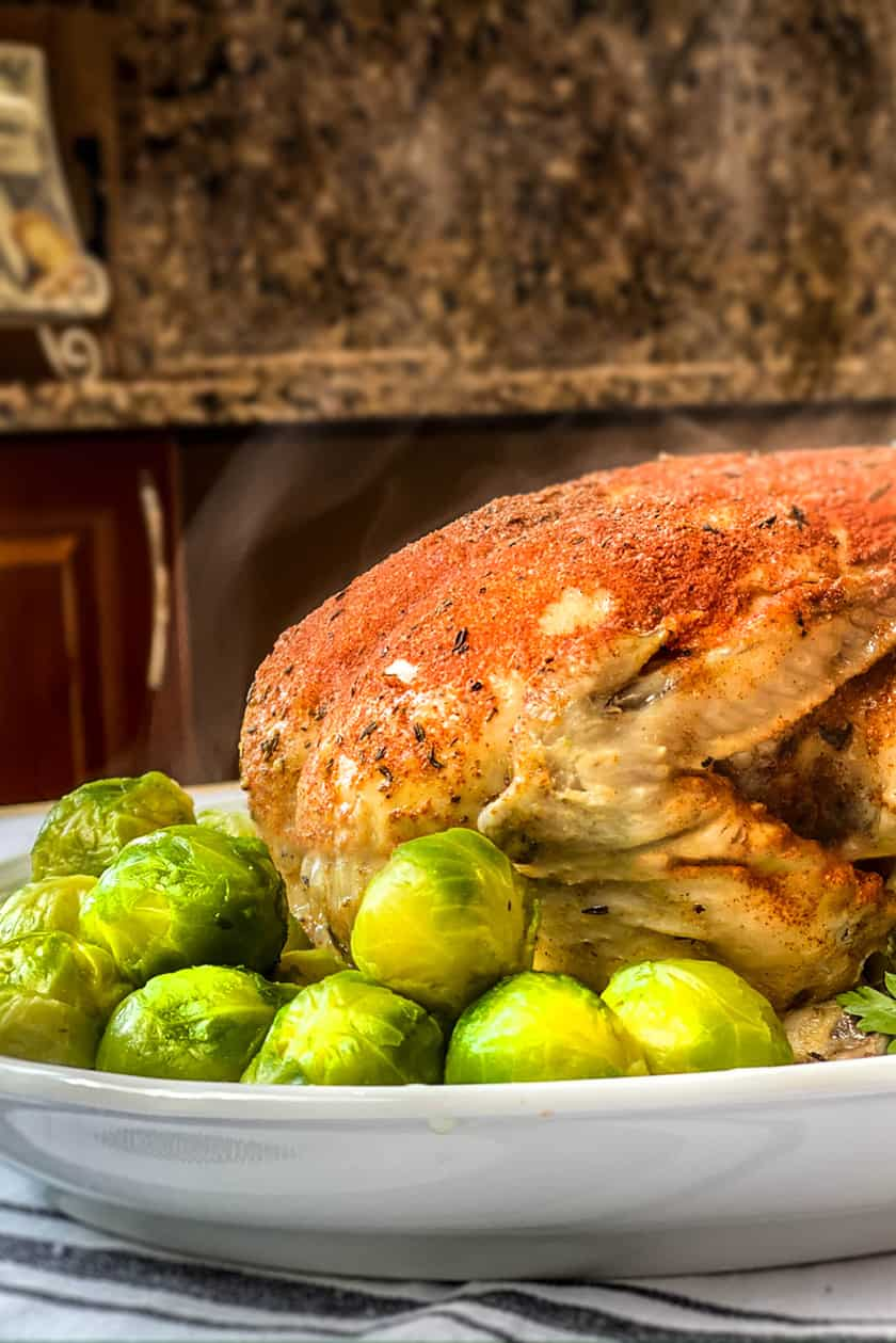 Cooked Rotisserie Chicken on a White Platter with Steam Rising
