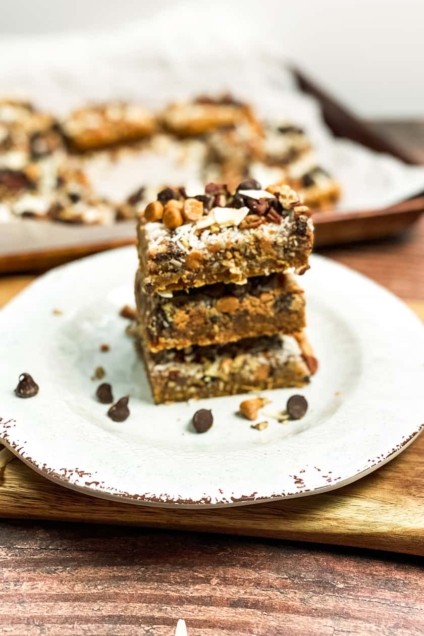 Stacked Magic Cookie Bars with Sheet Pan in the Background