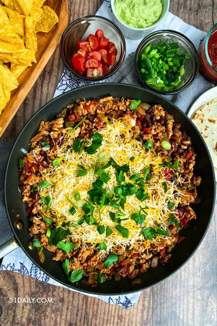 This Skillet Taco is the easiest, most delicious way to serve tacos at your next party. With a few simple, healthy ingredients, it's a go-to game day, Super Bowl, Friday night tradition. One Pot Easy Skillet Taco | 31Daily.com #mexican #tacos #skilletdinner #skillet #onepot #weeknightdinner #healthyrecipes #31Daily