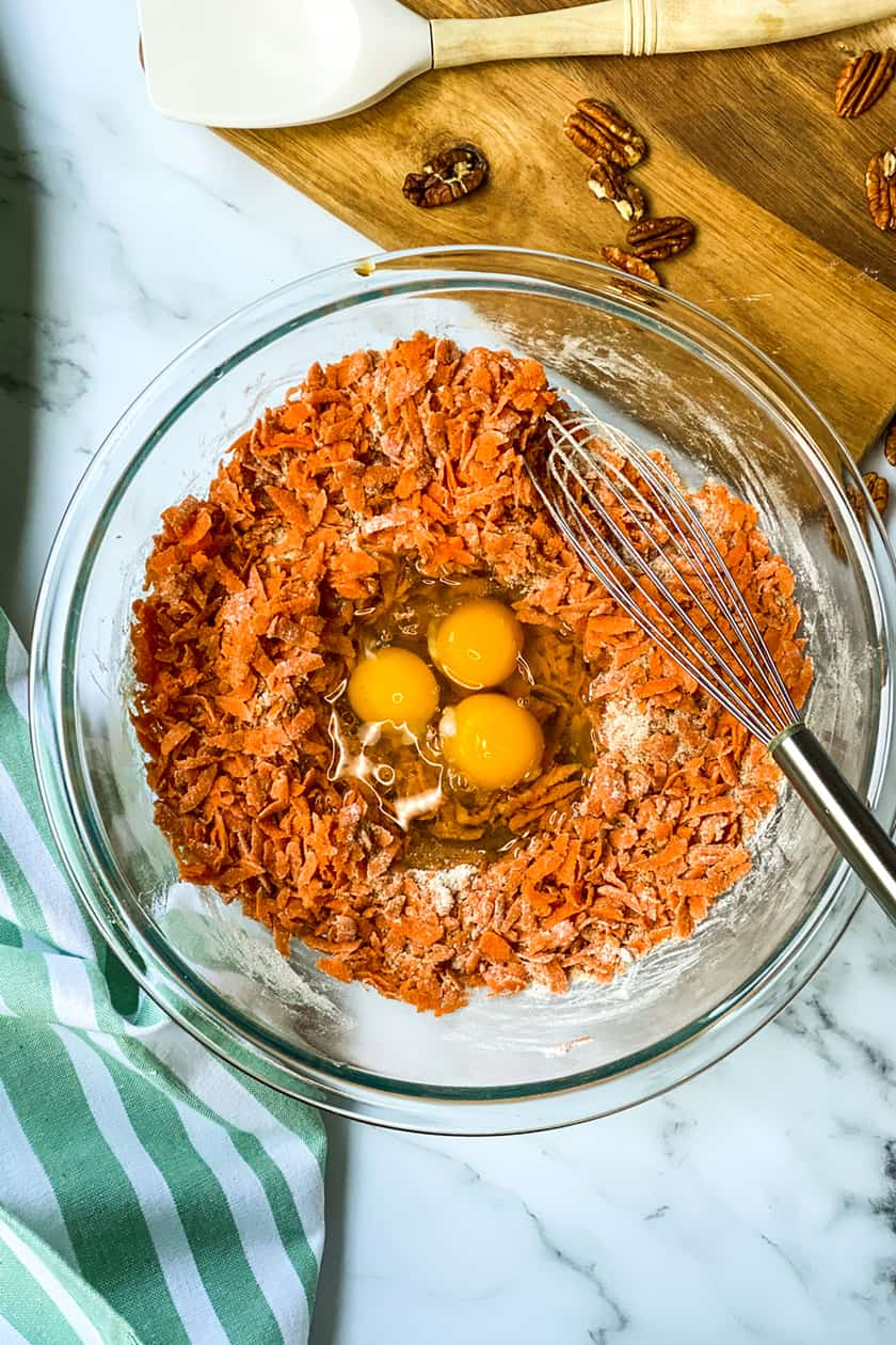 raw ingredients of shredded carrots and eggs in carrot cake loaf