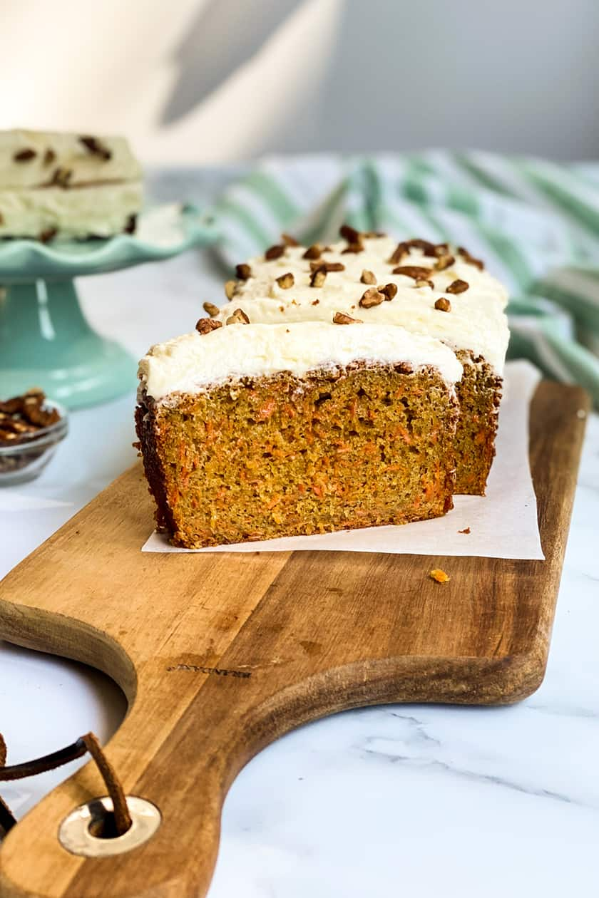 Sliced Carrot Cake Loaf on a Wooden Board with Slices in the Background