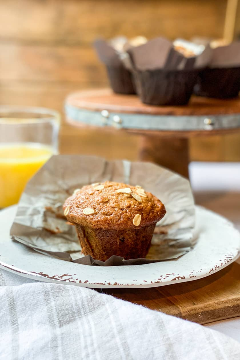 Unwrapped Morning Glory Muffin on a Plate with Orange Juice