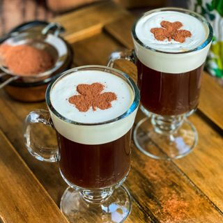 Two mugs of Irish Coffee with shamrock latte art