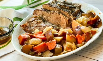 Side view of Italian Pork Roast and Sweet Potatoes on a White Platter