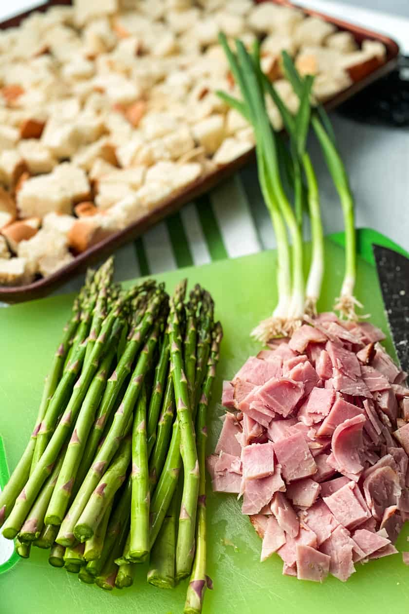 Strata Ingredients of bread cubes, asparagus spears, diced ham and scallions.