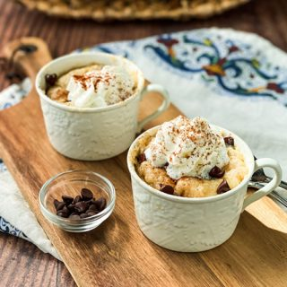 Closeup view of 2 Banana Mug Cakes topped with Whipping Cream