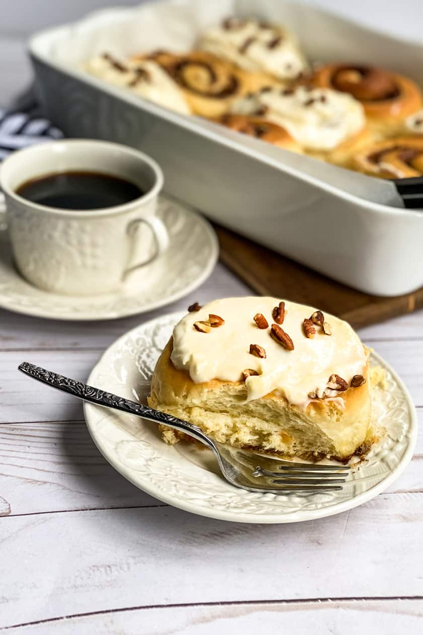 Homemade Cinnamon Roll on a White Plate with a Cup of Coffee