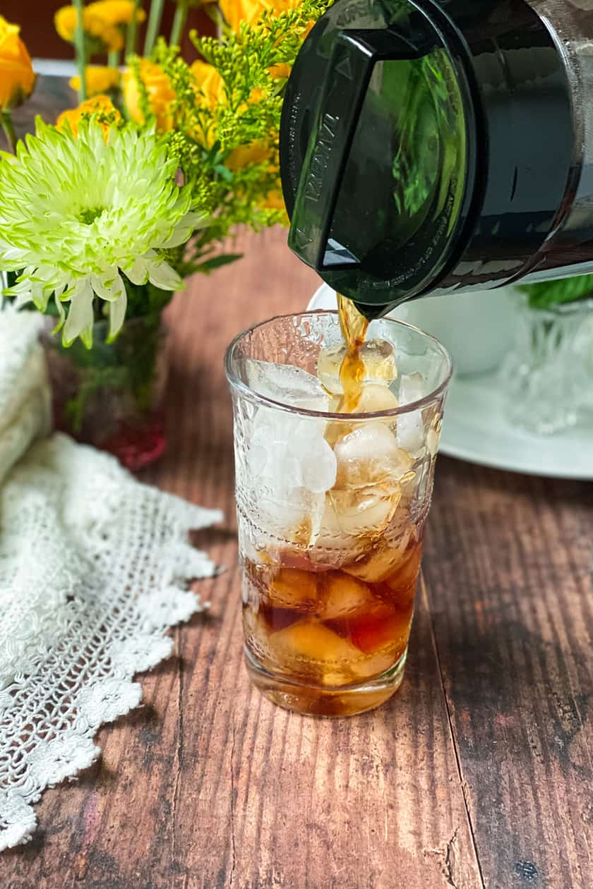 Tall glass filled with ice cubes and cold brew coffee being poured into it.