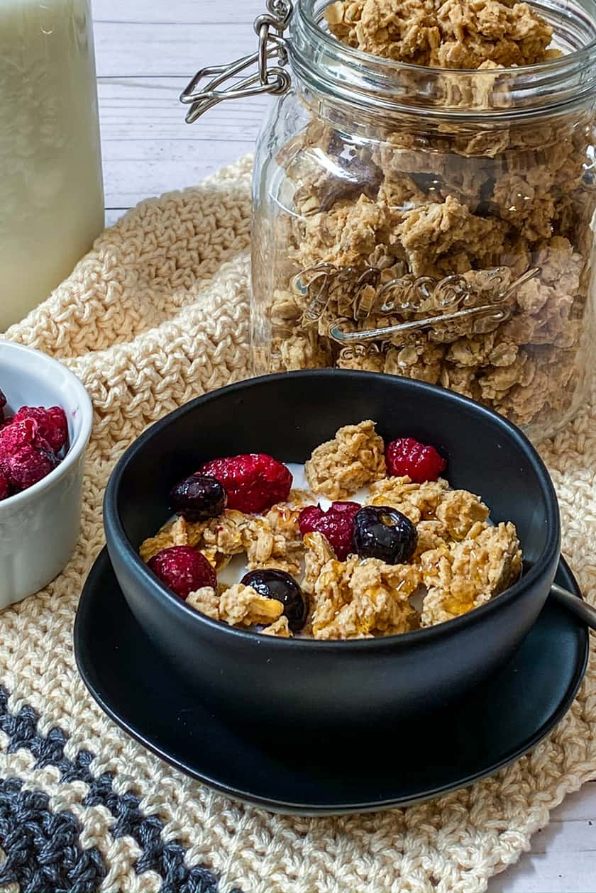 Peanut Butter Granola Clusters in a Black Bowl Drizzled with Honey and Topped with Berries