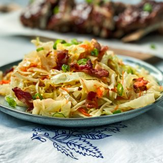 Hot Slaw with Bacon Dressing on a Plate with Instant Pot Ribs in the Background