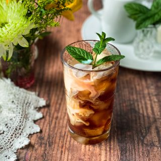Glass of Cold Brew Coffee with Vanilla Cream and a Mint Leaf