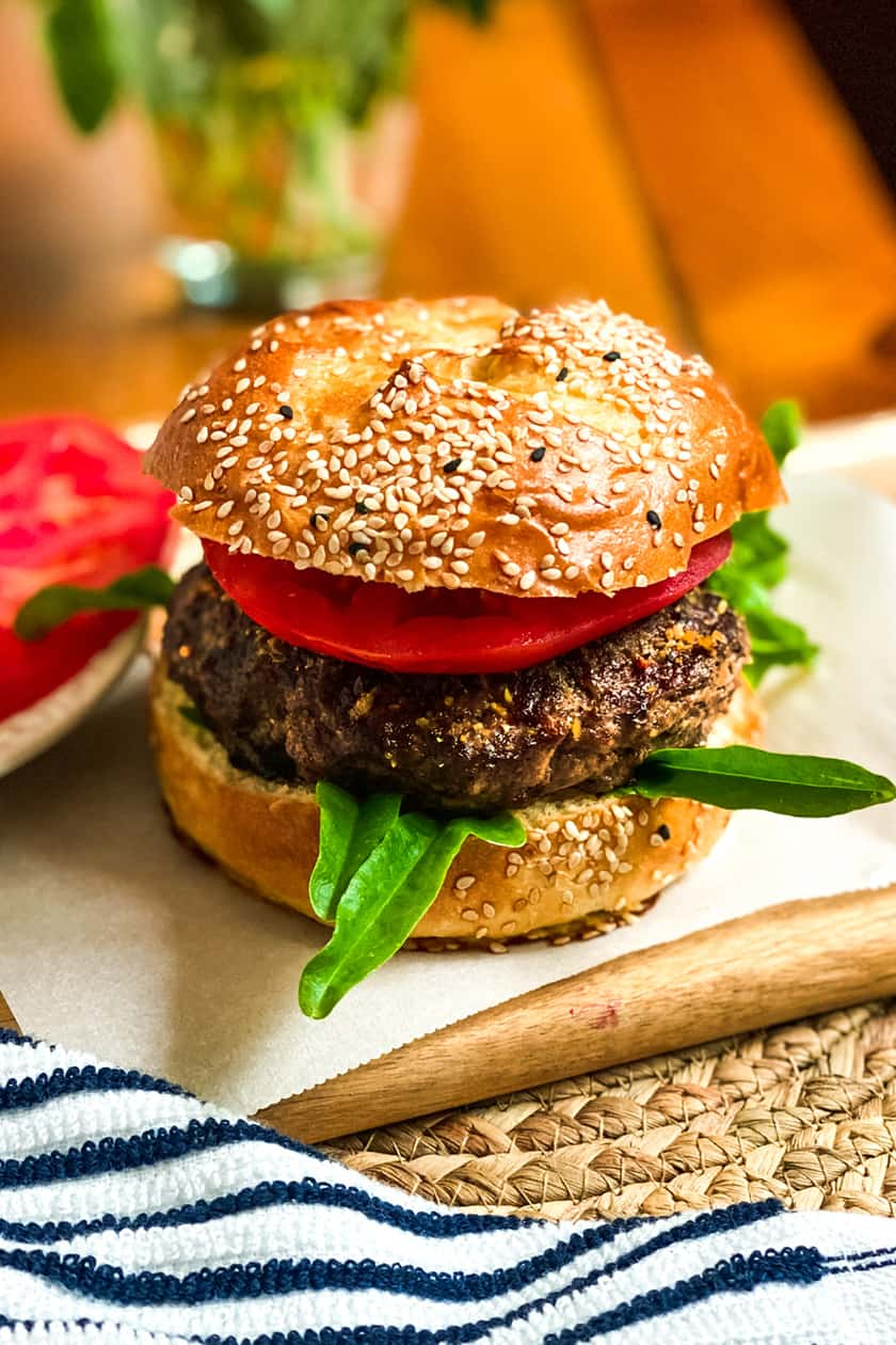 Grilled Burger on a Wood Cutting Board with Slices of Fresh Tomatocipe