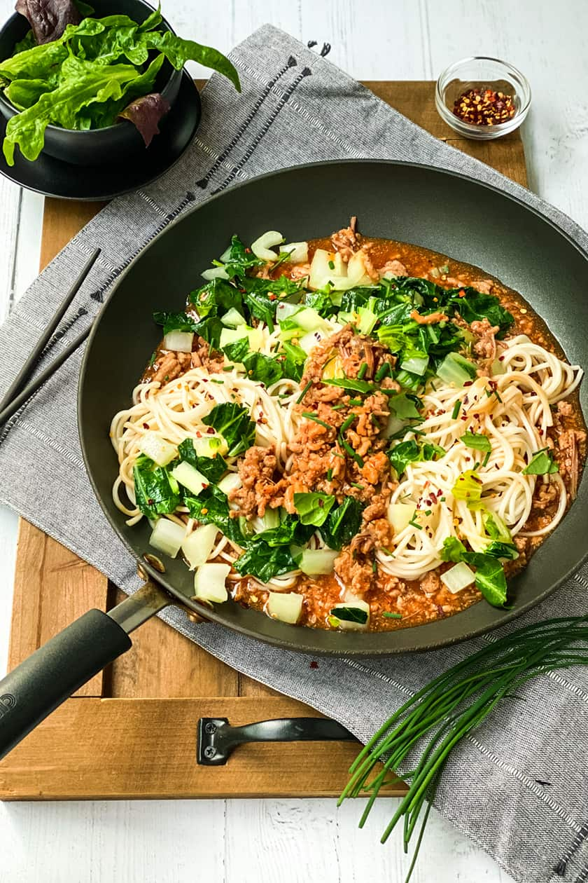 Side view of Ginger Pork Noodles with Bok Choy on a Wooden Board with Chopsticks