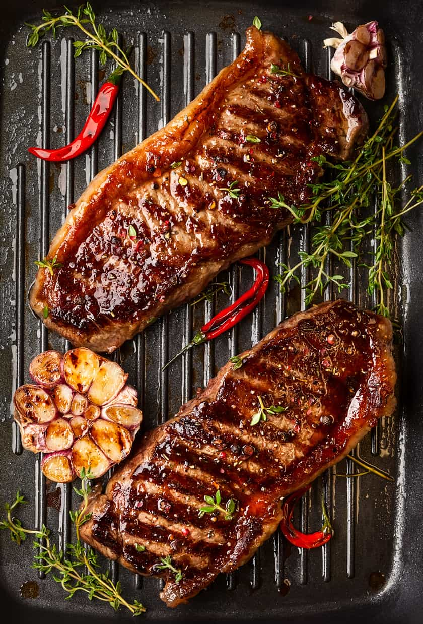Grilled Marinated Steaks on Grill Pan with Spices and Herbs