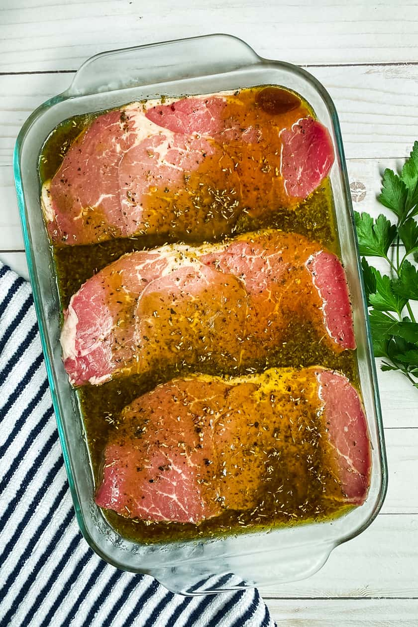 Raw steaks marinading in glass pan.