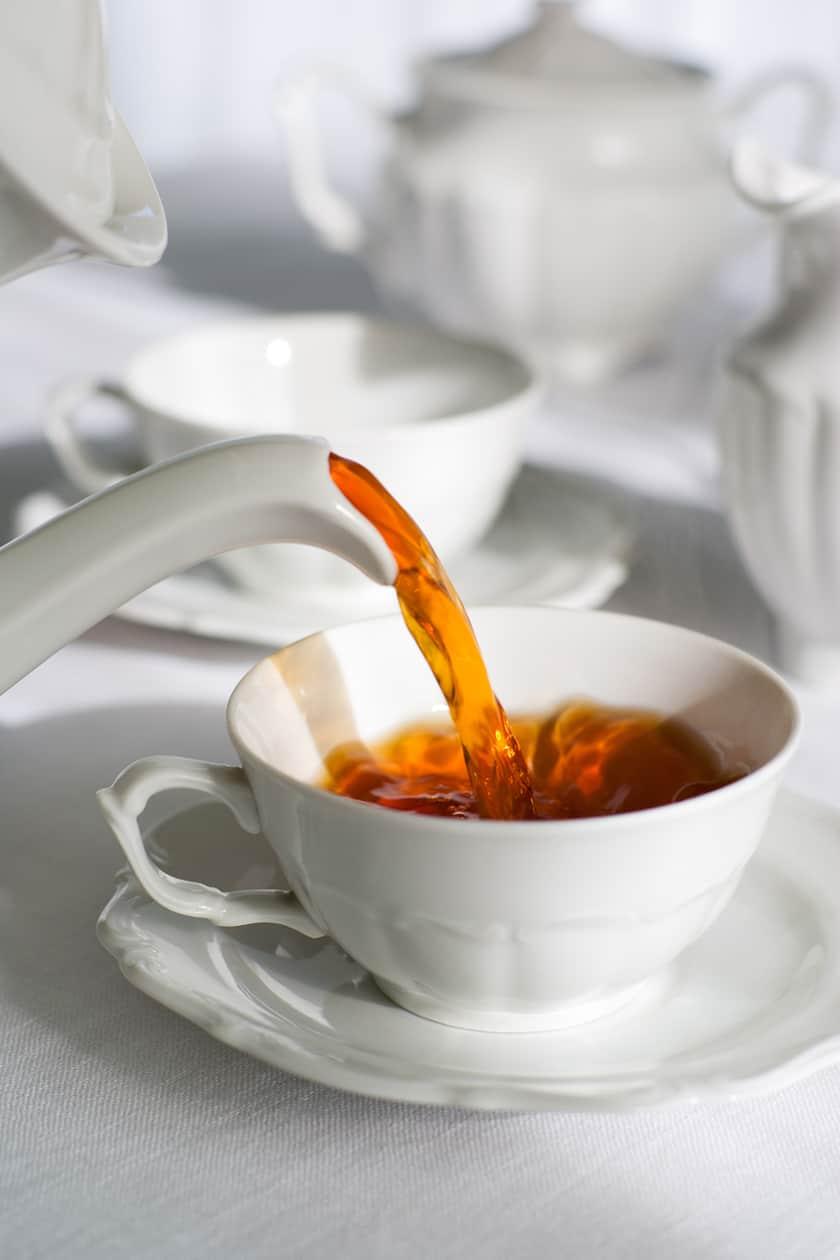 Porcelain teapot pouring black tea into a teacup