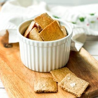 Homemade Crackers in a white ramekin on a wooden cutting board.