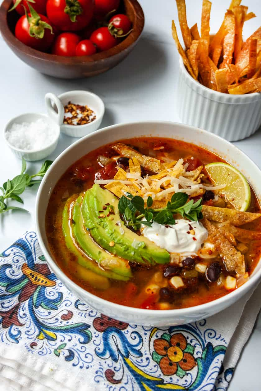 Side view of Instant Pot Chicken Tortilla Soup with toppings and fresh tomatoes.