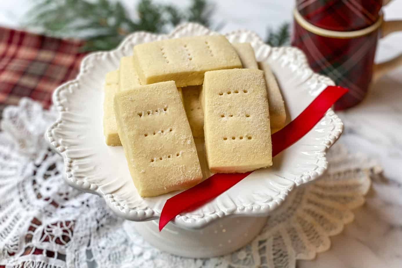 Shortbread cookies on a white platter with a red ribbon