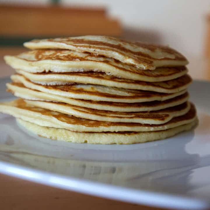 Stack of protein pancakes on a white plate