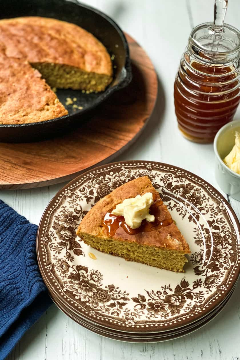 Slice of Skillet Bread on a Brown and White Plate with Butter and Drizzled Honey