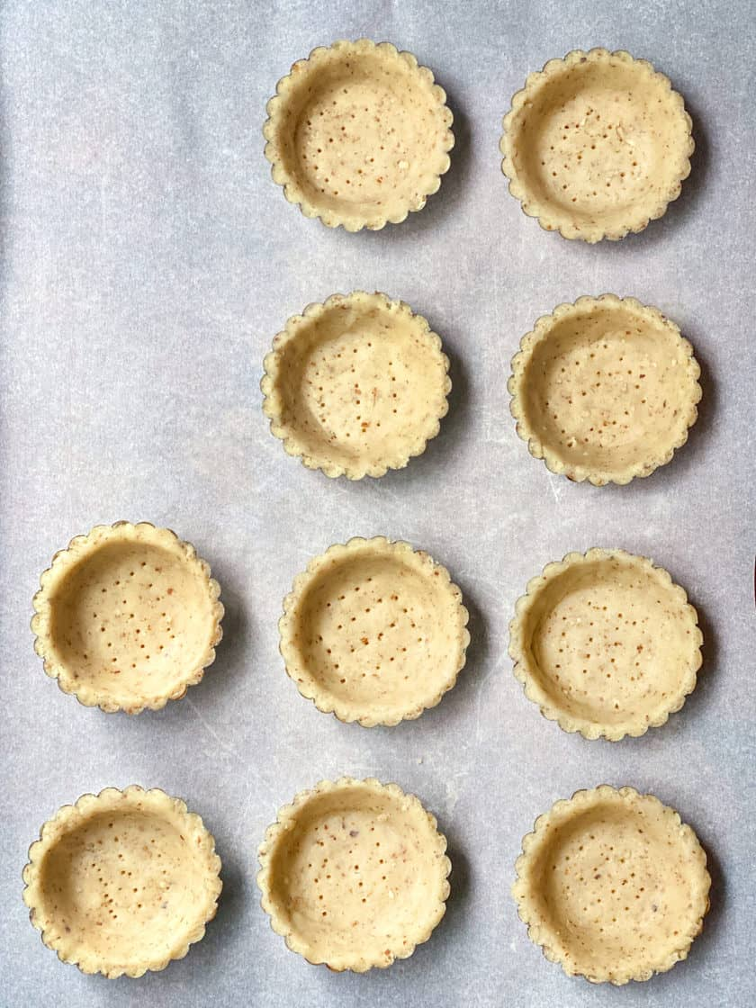 Unbaked Toasted Almond Shortbread Tart Shells on parchment paper