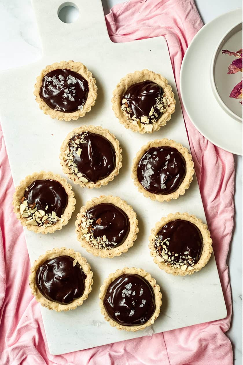 Chocolate Ganache Mini Tarts on a Marble Board with a Pink Background