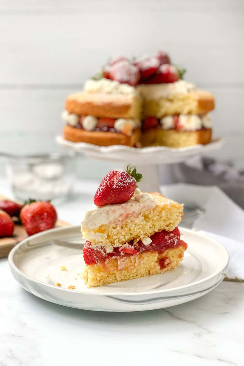 A slice of Victoria Sponge Cake in the foreground, topped with a fresh strawberry, on a white plate.